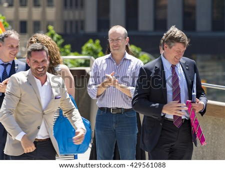 TORONTO,CANADA-MAY 31,2016:Pride Month: Mathieu Chantelois (cream jacket), executive director of Pride Toronto, offers a pink tie to John Tory mayor of Toronto