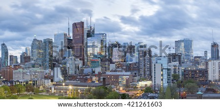 TORONTO, CANADA - May 15, 2016: Toronto Financial District skyscrapers and the CN Tower apex at the background at twilight- panoramic