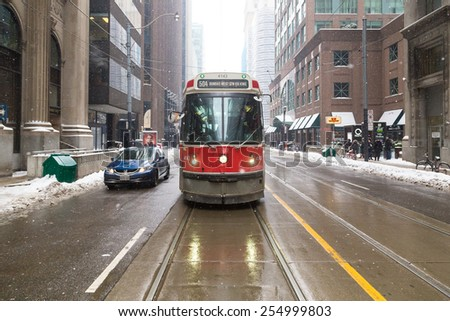 TORONTO, CANADA - 22ND FEBRUARY 2015: The front of a typical Toronto Streetcar during the winter. People can be seen.