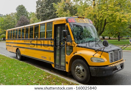 TORONTO, CANADA - OCTOBER 7, 2013: A bright yellow school bus parked outside in a park in Toronto on October 7 2013 - stock photo