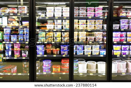 TORONTO, CANADA - OCTOBER 31, 2014: Different brands and flavors of ice cream on fridge shelves in a supermarket. Based on studies, half of the population in North America eat ice cream regularly. - stock photo