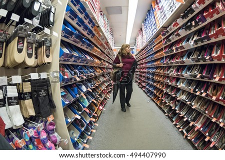 TORONTO,CANADA-OCTOBER 2, 2016: Woman buying shoes: Lady walking along the footwear section of a store.