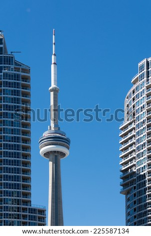 TORONTO,CANADA-SEPTEMBER 25, 2014:CN Tower among two buildings in Downtown Toronto. The CN Tower  is a 553.33 m-high concrete communications and observation tower in Downtown Toronto, Ontario, Canada. - stock photo