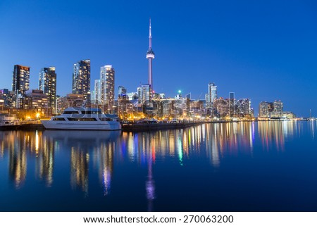 TORONTO, CANADA - 16TH APRIL 2015: A view of Toronto downtown at dusk showing buildings, condos, the CN Tower and boats. - stock photo