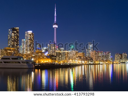 TORONTO, CANADA - 16TH APRIL 2015: A view of Toronto downtown at dusk showing buildings, condos, the CN Tower and boats.