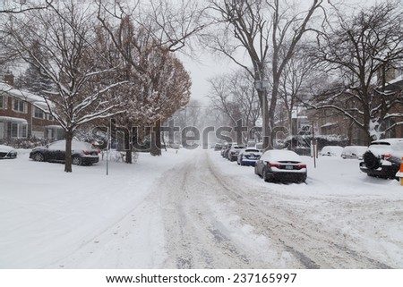 TORONTO, CANADA - 11TH DECEMBER 2014: A street in Toronto after a snow storm. Cars and buildings can be seen.