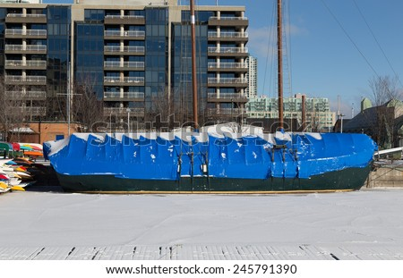 TORONTO, CANADA - 13TH JANUARY 2015: A boat covered in a plastic layer to protect it in the winter - stock photo