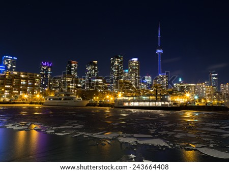 TORONTO, CANADA - 12TH JANUARY 2015: Part of the Toronto Skyline in the winter showing frozen water in the lake - stock photo