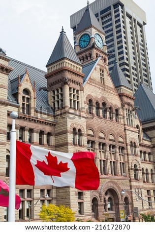 TORONTO, CANADA - 9TH SEPTEMBER 2014: Old Toronto City Hall during the day with the Canadian Flag flying - stock photo