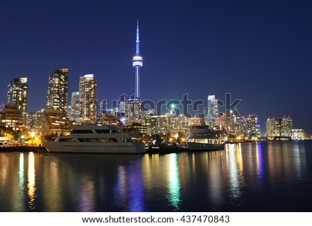 Toronto city skyline at night over lake with colorful reflections