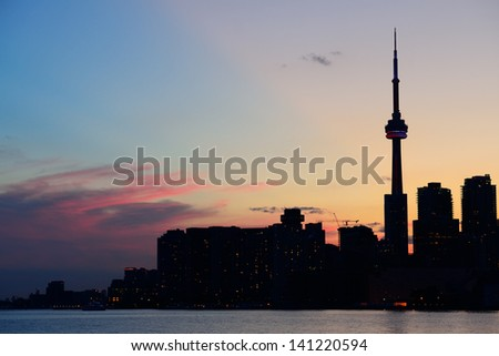 Toronto city skyline silhouette at sunset over lake with urban skyscrapers. - stock photo