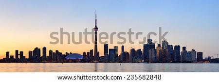 Toronto city skyline silhouette panorama at sunset over lake with urban skyscrapers. - stock photo