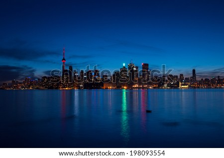 Toronto cityscape at night with reflections over the lake - stock photo