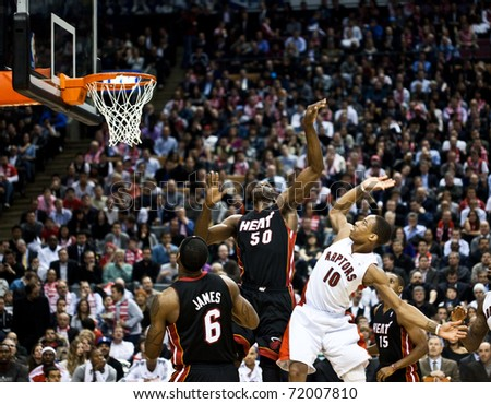TORONTO - FEBRUARY 16: LeBron James (L) participates in an NBA basketball game at the Air Canada Centre on February 16, 2011 in Toronto, Canada.  The Miami Heat beat the Toronto Raptors 103-95. - stock photo