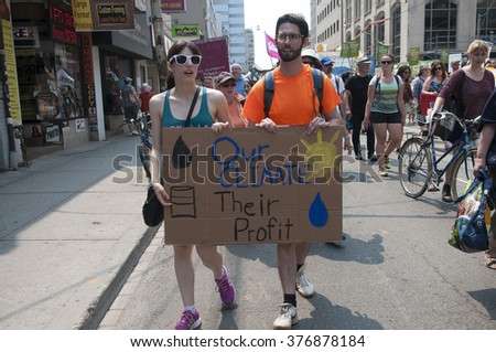 "TORONTO-JULY 5 : A couple walking with a sign which says ""our climate their profit""- an effort to denounce corporate greed during the Jobs,Justice and Climate rally on July  5, 2015 in Toronto,Canada."