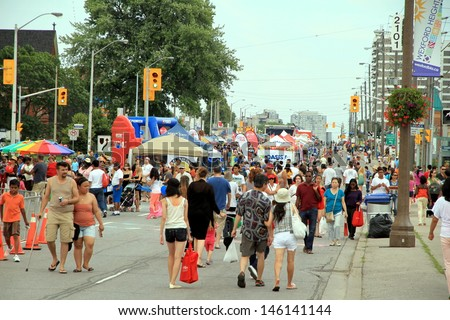 TORONTO - JULY 6: A diverse crowd at a street festival on July 6, 2013 in Toronto. About 50% of Toronto population belongs to a visible minority group. - stock photo