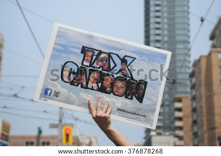 TORONTO - JULY 5 :  A  man holding a sign asking to tax carbon emission during the Jobs,Justice and Climate rally on July  5, 2015 in Toronto, Canada.
