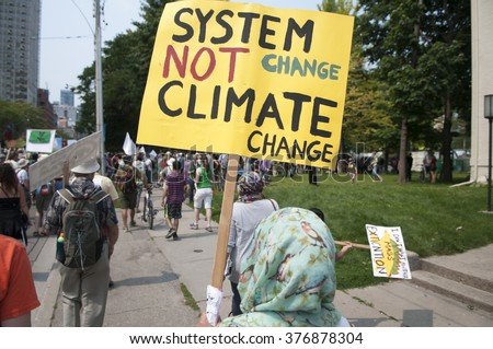 "TORONTO - JULY 5 : A Muslim woman wearing a ""hijab""  and carrying a sign saying ""system change not climate change ""during the Jobs,Justice and Climate rally on July  5, 2015 in Toronto, Canada."