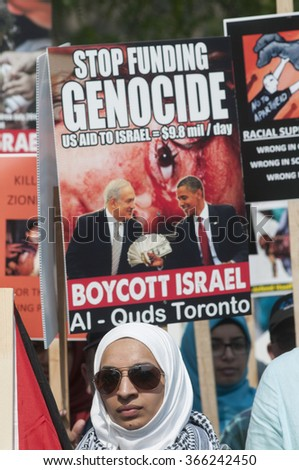 TORONTO-JULY 11: A Muslim woman wearing a veil standing in front of an anti US-Israel relationship banner during the Al-Quds day rally on July 11, 2015 in Toronto,Canada. - stock photo