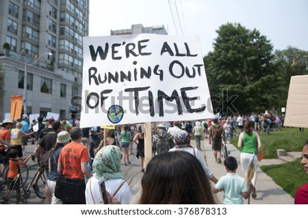 TORONTO - JULY 5 :  A woman holding signs to state that we have to act on climate change now during the Jobs,Justice and Climate rally on July  5, 2015 in Toronto, Canada.