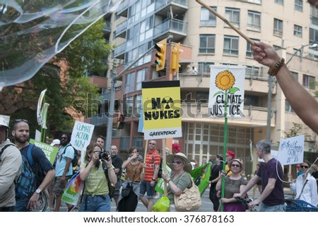 "TORONTO - JULY 5 : A woman protester with a sign saying ""no nukes""  during the Jobs,Justice and Climate rally on July  5, 2015 in Toronto, Canada."