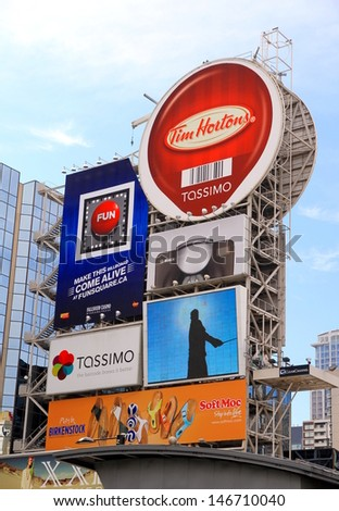 TORONTO - JULY 12: Billboards in Dundas Square on July 12, 2013 in Toronto. Dundas Square is a commercial and public square that hosts many events and it is one of Toronto's main attraction. - stock photo