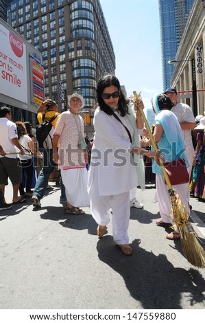 TORONTO - JULY 13:  Followers  cleaning the holy path of the chariot -which is considered sacred during the 41st Annual Festival of India on July 13, 2013 in Toronto-Canada. - stock photo