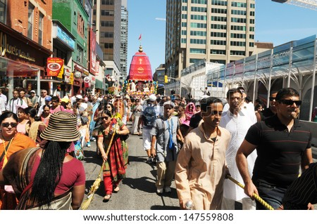 TORONTO - JULY 13:  Followers of ISCON  marching in rally pulling the sacred rope of the Chariot during the 41st Annual Festival of India on July 13, 2013 in Toronto-Canada. - stock photo