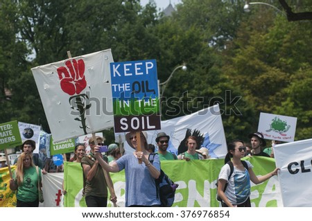 "TORONTO - JULY 5 :   Participants of various ages with signs saying ""Keep the oil in the soil ""during the Jobs,Justice and Climate rally on July  5, 2015 in Toronto, Canada."