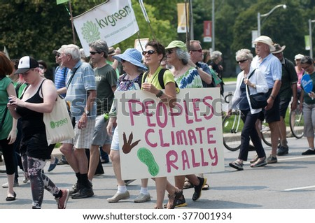 TORONTO - JULY 5 : People's climate rally- A person walking with this sign  during the Jobs,Justice and Climate rally on July  5, 2015 in Toronto, Canada.