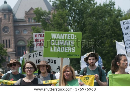 "TORONTO - JULY 5 :  People with signs demanding ""climate leaders"" during the Jobs,Justice and Climate rally on July  5, 2015 in Toronto, Canada."