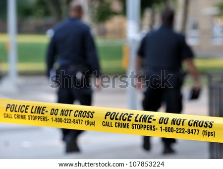 TORONTO-JULY 17: Police line Do not cross tape with two officers in the background at the crime scene where shooting leaves 2 dead and 21 injured on July 17, 2012 in Toronto - stock photo