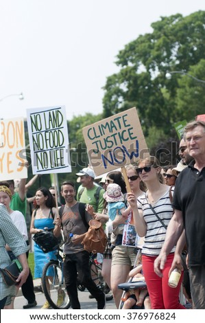 TORONTO - JULY 5 :  Protesters with signs  asking for justice towards climate care during the Jobs,Justice and Climate rally on July  5, 2015 in Toronto, Canada.