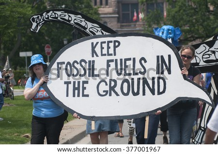 TORONTO - JULY 5 : Two women carrying a installation asking to keep fossil fuels in the ground during the Jobs,Justice and Climate rally on July  5, 2015 in Toronto, Canada.