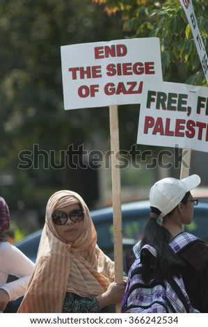 TORONTO-JULY 11: Women walking with signs to  free Palestine during the Al-Quds day rally on July 11, 2015 in Toronto,Canada. - stock photo