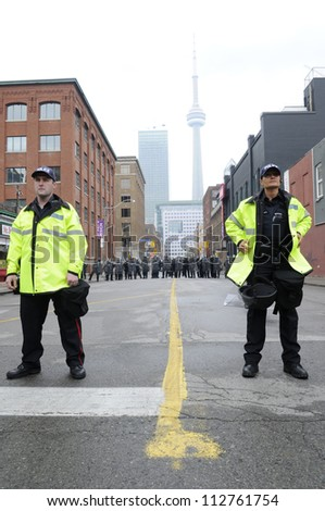 TORONTO-JUNE 26:  A  group of Toronto police officers standing in front of a perimeter formed by the riot police  during the G20 Protest on June 26 2010 in Toronto, Canada. - stock photo
