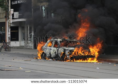TORONTO-JUNE 26:  A police car burning on queen street during the G20 Protest on June 26, 2010 in Toronto, Canada. - stock photo