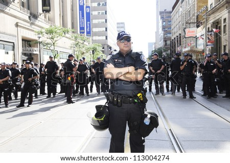 TORONTO-JUNE 28:  A police officer keeping a close and careful eye on the people on the streets  during the G20 Protest on June 28, 2010 in Toronto, Canada. - stock photo