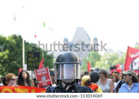 TORONTO-JUNE 25:  A Police officer wearing protective helmet guiding a huge rally through the streets of Toronto during the G20 Protest on June 25, 2010 in Toronto, Canada.