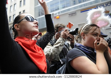 TORONTO-JUNE 26:  A protester chanting slogans while another one talking on her cell phone   during the G20 Protest on June 26, 2010 in Toronto, Canada.