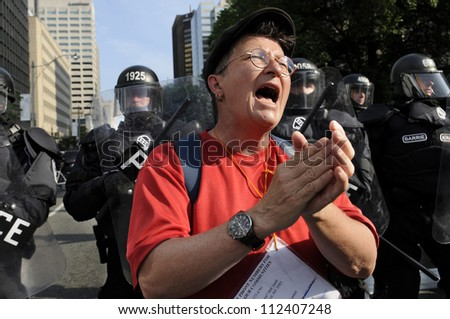 TORONTO-JUNE 25: A protester clapping and initiating her fellow protesters during the G20 Protest on June 25, 2010 in Toronto, Canada. - stock photo