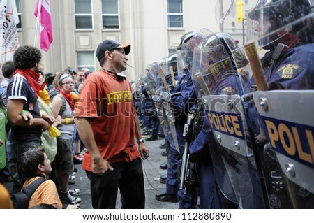 TORONTO-JUNE 26:   A protester cranking a joke on the riot police during the G20 Protest on June 26, 2010 in Toronto, Canada.