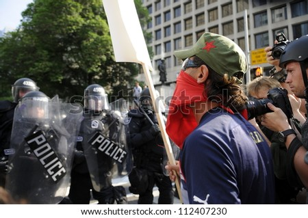 TORONTO-JUNE 25:  A protester wearing a bandana arguing with the police during the G20 Protest on June 25, 2010 in Toronto, Canada.
