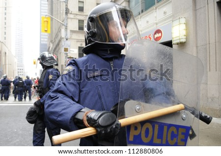 TORONTO-JUNE 26:  A riot police officer hitting his riot shield with his baton during the G20 Protest on June 26, 2010 in Toronto, Canada.