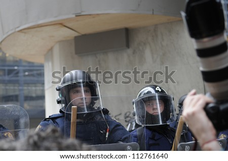 TORONTO-JUNE 26:   A  riot police officer looks at a photographer  with suspicion during the G20 Protest on June 26 2010 in Toronto, Canada.