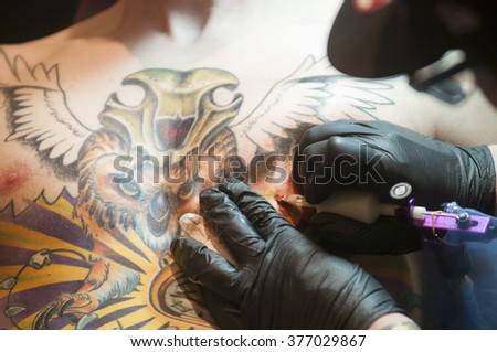 TORONTO - JUNE 19 :  A tattoo artist working on a tattoo on his clients chest during the Toronto Tattoo convention on June 19, 2015 in Toronto, Canada.