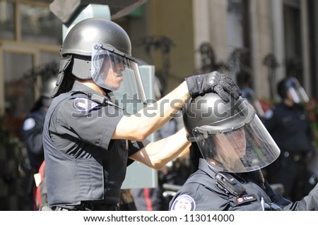 TORONTO-JUNE 25:   A Toronto police officer helps his fellow female colleague to fix her helmet during the G20 Protest on June 25, 2010 in Toronto, Canada. - stock photo