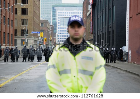 TORONTO-JUNE 26:   A Toronto police officer keeps a close eye on the rally during the G20 Protest on June 26 2010 in Toronto, Canada. - stock photo