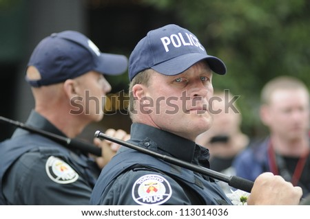 TORONTO-JUNE 26:  A visibly angry police officer looking for suspects after one of the police car was torched during the G20 Protest on June 26, 2010 in Toronto, Canada.
