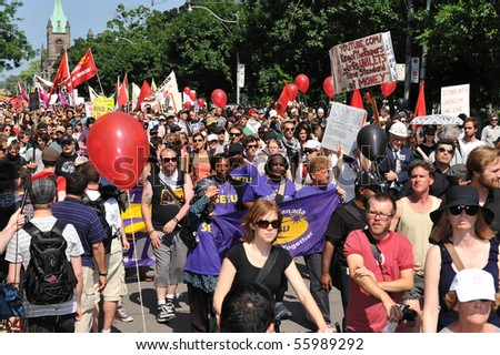 TORONTO-JUNE 25: Activists march along the streets of downtown Toronto while participating in a protest ahead of the G20 summit on June 25, 2010 in Toronto, Canada. - stock photo